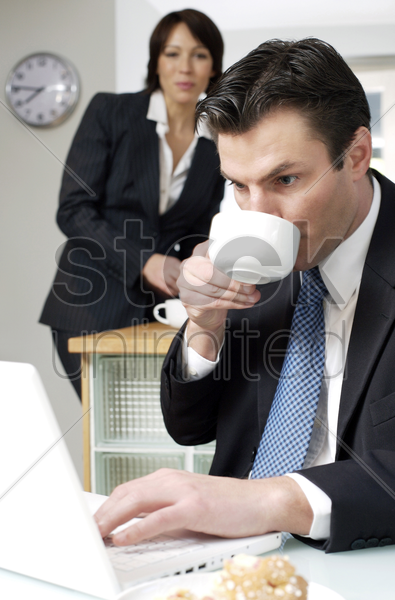 businessman drinking coffee while using laptop with his wife in the background stock photo