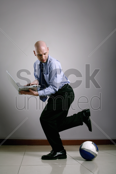 businessman playing football while using laptop stock photo