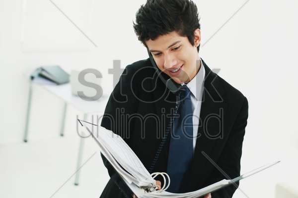 businessman talking on the phone while reading document a file stock photo