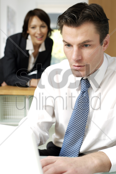 businessman using laptop with his wife in the background stock photo