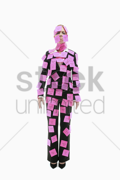 businesswoman covered with adhesive notes looking sad stock photo