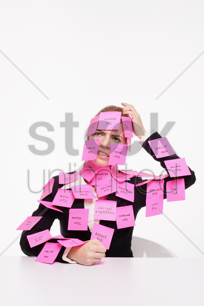 businesswoman covered with adhesive notes scratching her head stock photo