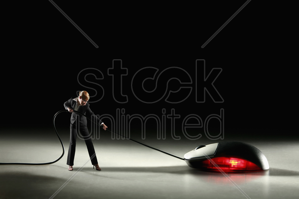 businesswoman pulling computer mouse stock photo