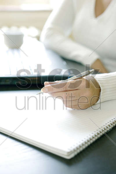 businesswoman writing on a book while using laptop stock photo