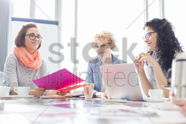 businesswomen working at desk in creative office stock photo