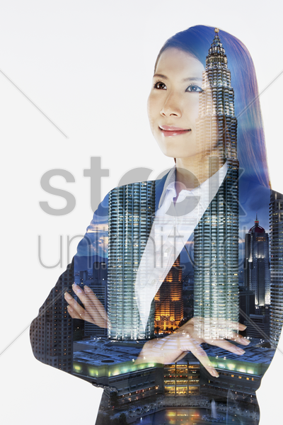 cheerful businesswoman standing with arms crossed, smiling stock photo