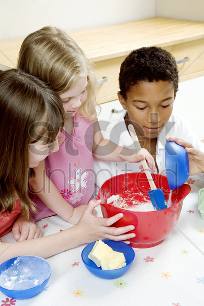 children baking cake in the kitchen stock photo