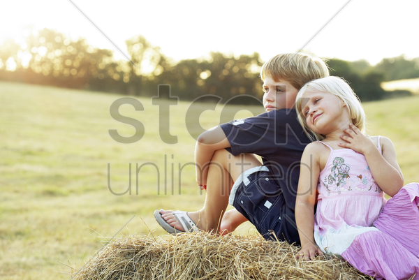 children sitting on a haystack stock photo