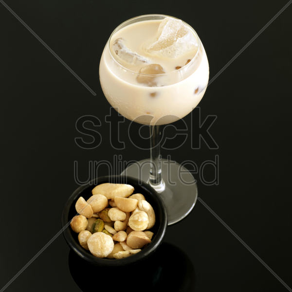 cream liqueur with ice and bowl of mixed nuts stock photo