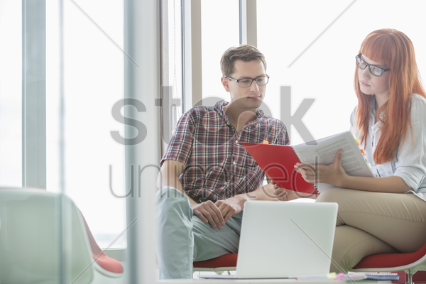 creative colleagues reading file in office stock photo