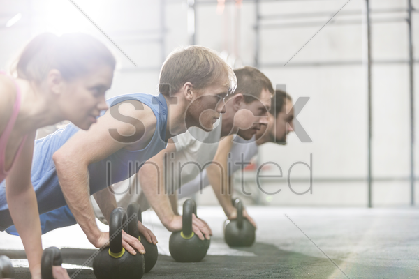 dedicated people doing pushups with kettlebells at crossfit gym stock photo