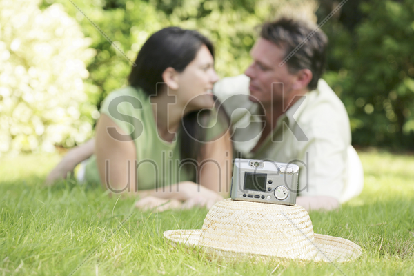 digital camera on a hat with couple lying forward on the field stock photo
