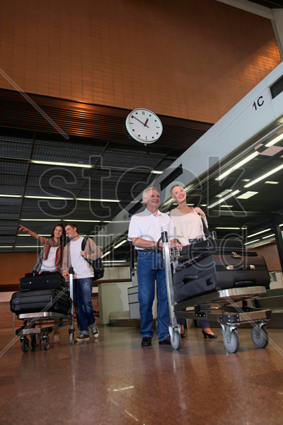 family arriving at the airport of their destination, pushing luggage trolleys stock photo