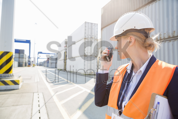 female engineer using walkie-talkie in shipping yard stock photo