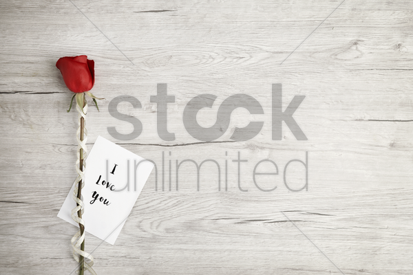 flatlay of wooden background with rose and romantic message stock photo