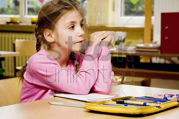 girl daydreaming in the classroom stock photo