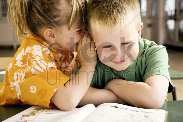 girl whispering something into boy's ear stock photo