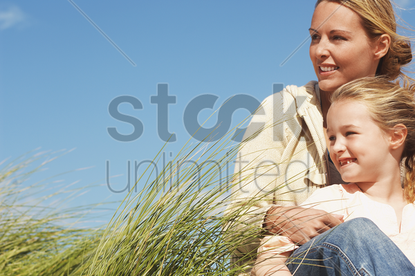 happy mother and daughter sitting together in long grass against blue sky stock photo