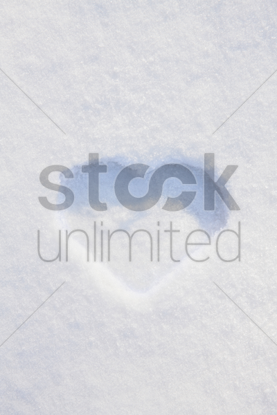 heart-shaped print in snow stock photo