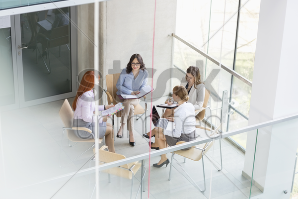 high angle view of businesswomen discussing in office stock photo