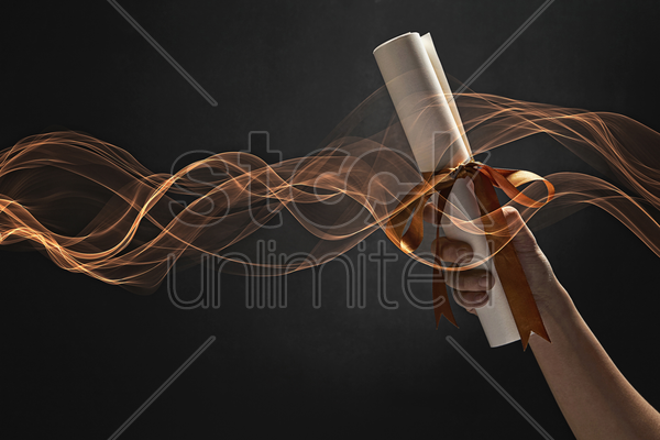human hand holding a graduation scroll stock photo