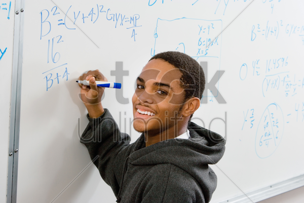 male student writing equations on whiteboard (portrait) stock photo