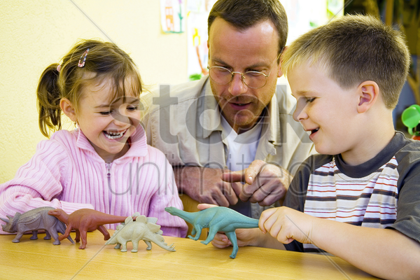 male teacher showing his students some dinosaur figurines stock photo