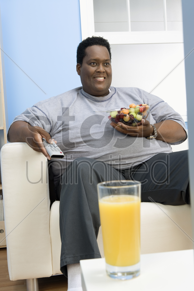 man eating bowl of fruit stock photo
