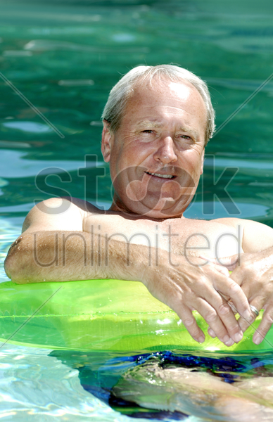 man floating on the swimming pool stock photo
