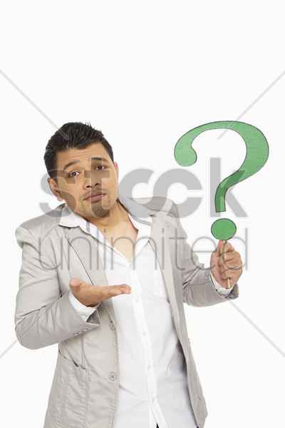 man holding up a question mark symbol stock photo