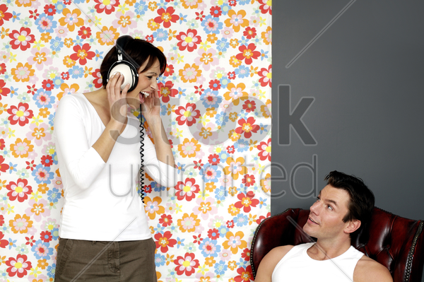 man looking at his wife listening to music on the headphones stock photo