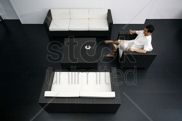 man resting in a spacious living room stock photo