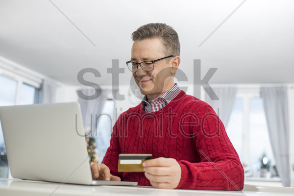 mature man using credit card and laptop to shop online during christmas stock photo