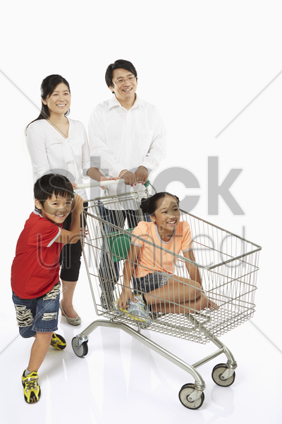 parents pushing a shopping cart with children in tow stock photo