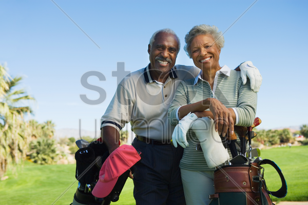 senior couple in golf course smiling (portrait) stock photo