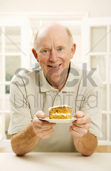 senior man holding a plate of cake stock photo