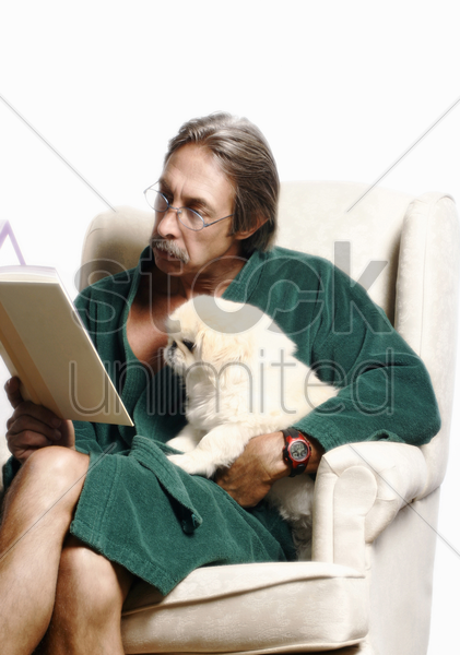 senior man hugging his dog while reading book on the couch stock photo