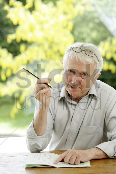 senior man playing sudoku stock photo