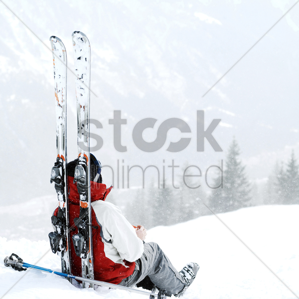 skier sitting alone stock photo
