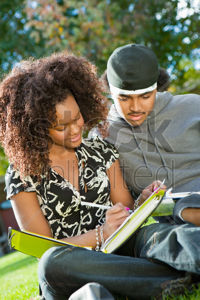 student couple studying outdoors stock photo