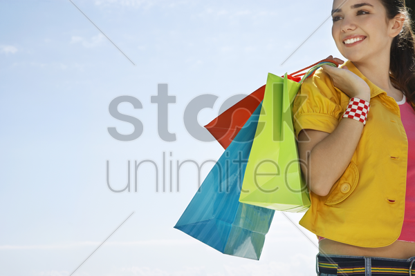 teenage girl carrying shopping bags outdoors stock photo
