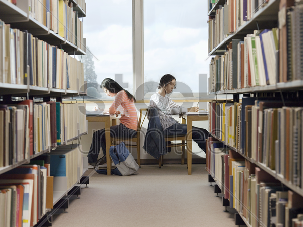 teenagers doing homework in library stock photo