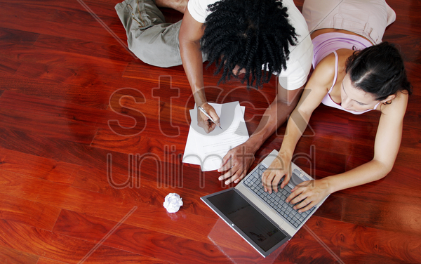 top view of an african american guy and a lady sharing a laptop on the floor stock photo