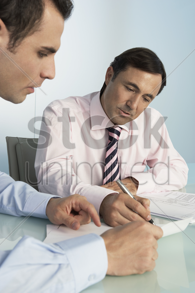 two business men working at table in office stock photo