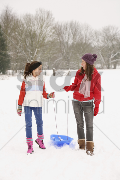 two girls walking in the snow stock photo
