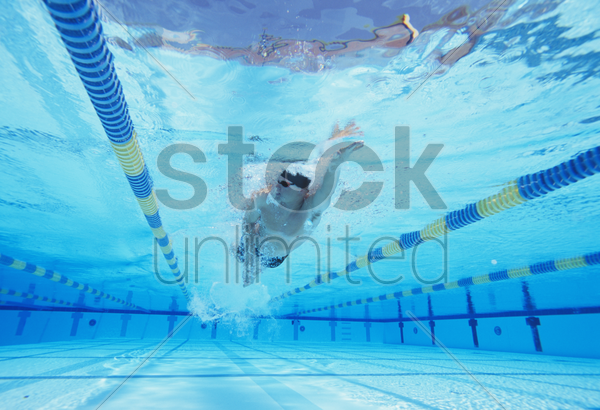 underwater shot of young male athlete swimming in pool stock photo