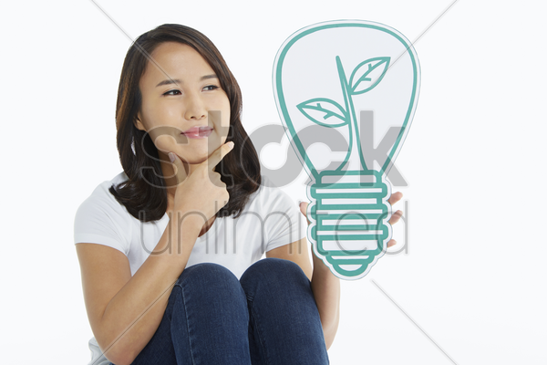 woman holding up a light bulb made of cardboard stock photo