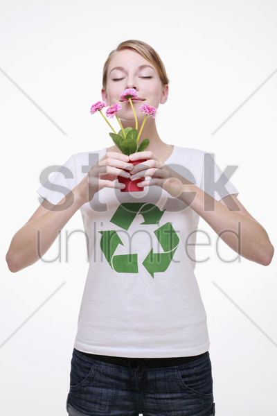 woman with recycling symbol on her t-shirt holding a potted plant and smelling it stock photo