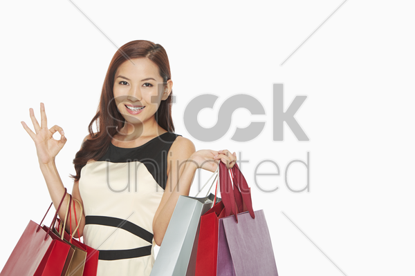 woman with shopping bags showing hand gesture stock photo