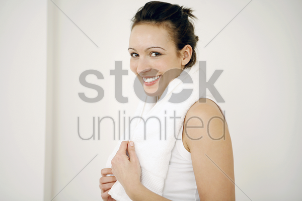woman with towel around her neck smiling at the camera stock photo